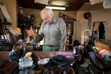 Throughout the day John hosts locals who come to his shop to discuss sports, politics, and local news.