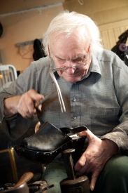 Carefully repairing the heel of a woman's shoe.